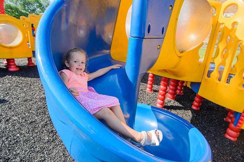 Colorful slide and girl playing on playground