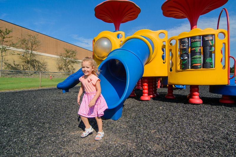 Young girl on slide smiling