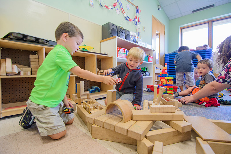 Boys playing with building blocks together inside