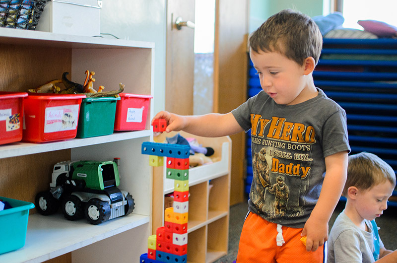 Boy playing with building blocks inside