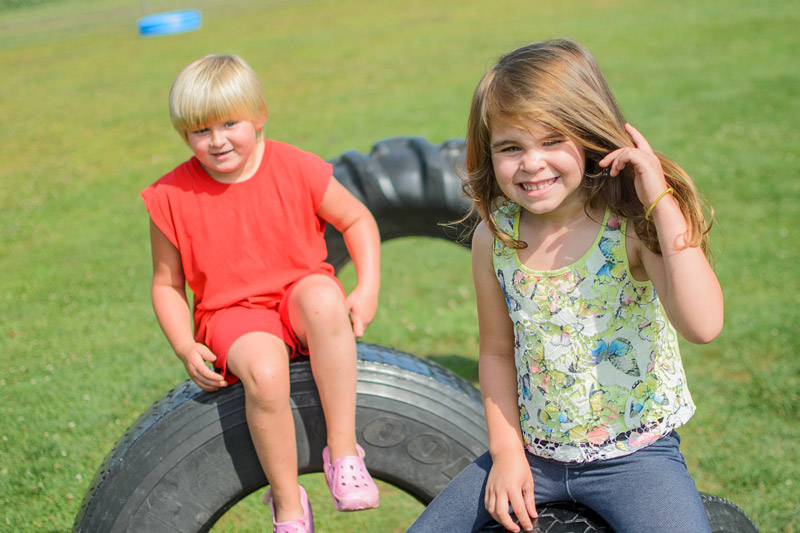 Children sitting on tires on playground